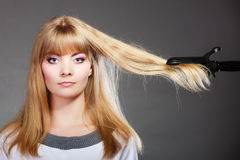 Woman making hairstyle with hair iron Stock Photos