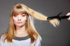Woman making hairstyle with hair iron Royalty Free Stock Photo