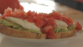 Woman preparing healthy breakfast with avocado on roasted bread, eggs and tomato. Woman making health breakfast in the kitchen in the morning hours by spreading stock footage