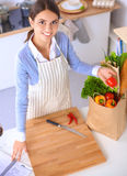 Woman making healthy food standing smiling in kitchen Royalty Free Stock Images