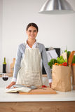 Woman making healthy food standing smiling in kitchen Stock Photo
