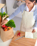 Woman making healthy food standing smiling in kitchen Royalty Free Stock Photography