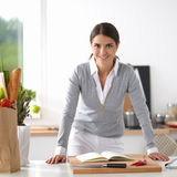 Woman making healthy food standing smiling in kitchen Stock Photos