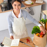 Woman making healthy food standing smiling in kitchen Royalty Free Stock Image