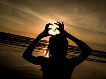 Woman making heart at the beach stock images