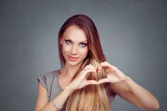Woman making a heart gesture with her fingers hands royalty free stock images