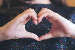 A woman making heart hand sign though her shirt Royalty Free Stock Photography