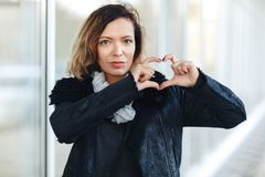 Fashion pretty sweet young woman woman in a leather jacket, black jeans posing in front of mirrored windows.making heart hands, Fe. Woman making heart hands stock photos