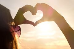 Woman making heart with hands in sunset. Love symbol in sunny summer night. Happy and carefree lifestyle Stock Photos