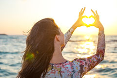 Woman making heart with her hands round the sun in sunset Royalty Free Stock Photos