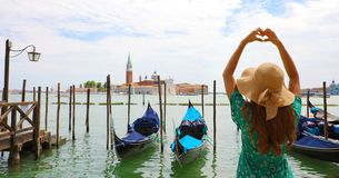 Woman making heart shape with hands on the beautiful view of Venice Lagoon, Italy royalty free stock photo