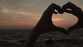 Woman making heart shape sign with hands at sunset Girl holding up love symbol. Gesture with orange sun flare stock video