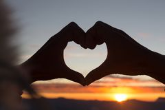 Woman making heart shape during sun rise, God is love concept, Heart shape, Mountain tourism, Symbol of love, The manifestation of. Love, Expression of feelings stock image