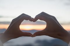 Woman making heart shape during sun rise, God is love concept, Heart shape, Mountain tourism, Symbol of love, The manifestation of. Love, Expression of feelings royalty free stock photography