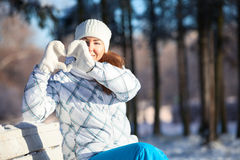 Woman making heart shape with white mittens in sunlight at winter Royalty Free Stock Images