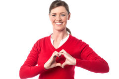 Woman making heart symbol with hands Stock Photos