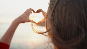 Woman making heart symbol with her hands during sunset on beach. Slow motion. Woman making heart symbol with her hands during sunset on beach with lihgthouse stock footage