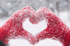 Woman Making Heart Symbol With Snowy Hands Stock Photo