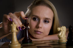 Woman making her move in chess. Woman playing chess making her move with focus on the chess piece Stock Photography