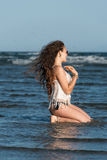 Woman making her wet in sea. Woman with long curly hair wear bottom bikini and white shirt, kneeling in sea water and making her wet. Sea and sky as background Stock Images