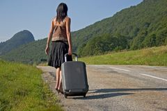 Woman making of hitch-hiking. Woman on the roadside in mountain Royalty Free Stock Images