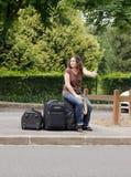 Woman making hitchhiking. Sitting on his luggage Stock Image