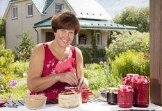 Woman making home made jam from berries Stock Photo