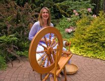 Woman Making Homespun Yarn. This artisan woman is hand crafting wool into homespun yard using a spinning wheel in a beautiful garden setting Stock Photo