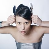 Woman making horns with silver knife and horns. A pretty woman putting silver knife and fork  on her head like horns and frowning Royalty Free Stock Photography