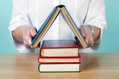 Woman making a house from books stock images