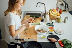 Woman making kebabs from meat and vegetable on chopping board in kitchen. Cropped view of woman threading chicken meat and vegetable pieces on skewer on wooden Stock Photos