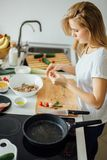 Woman making kebabs from meat and vegetable on chopping board in kitchen. Top view of cropped female body sticking chicken bits, pickled in rosmary and oil on Stock Photos