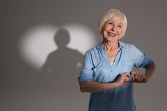 Woman making love gesture and standing in studio with heart shaped shadow Royalty Free Stock Images