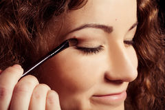 Woman is making make-up. With brush tool Stock Image