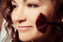Woman is making make-up. With brush tool Royalty Free Stock Photography