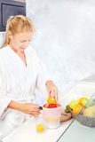 Woman making morning juice in kitchen. Pretty woman making morning juice in kitchen stock images