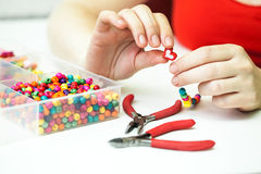 Woman making necklase from colorful plastic beads on light background Royalty Free Stock Images