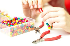 Woman making necklase from colorful plastic beads on light background Stock Photos