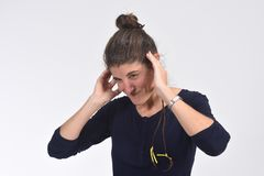 Woman making noise hurting her ears on white background.  royalty free stock photography
