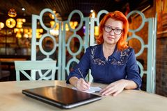 A woman is making notes in a notebook at a table in a cafe with a closed laptop and straight. A woman, aged, red-haired, in a blue dress and glasses, makes notes Royalty Free Stock Photography