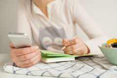Woman making notes in notepad with healthy food on table Royalty Free Stock Photos