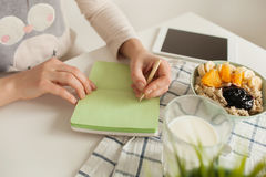 Woman making notes in notepad with healthy food on table Stock Photography