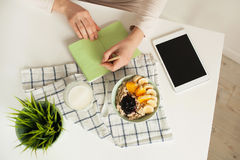 Woman making notes in notepad with healthy food on table Royalty Free Stock Image