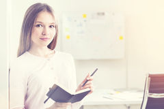 Woman making notes. Pretty young businesswoman making notes in notepad on modern office background. Toned image Stock Photography