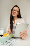 Woman making notes with tablet and healthy food on table Stock Images