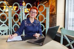 Woman is making notes in a tablet with papers and is looking forward at the table with a laptop in a cafe. A woman in age, in a blue dress, red-haired with Royalty Free Stock Photos