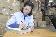 Woman Making Notes In Warehouse Stock Image