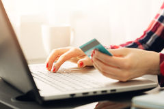 Woman making online payment with credit card. On laptop Royalty Free Stock Image