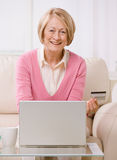 Woman making online purchase on laptop wit. Happy senior woman making online shopping purchase on laptop with credit card Royalty Free Stock Photo