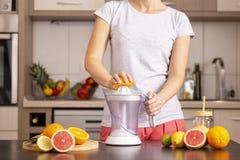 Woman making orange juice royalty free stock photography